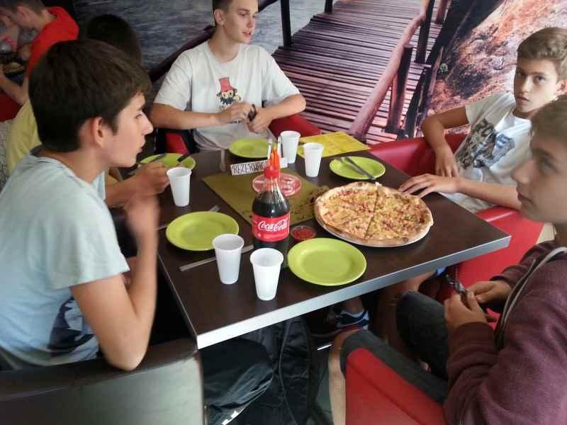 chłopcy jedzą pizzę