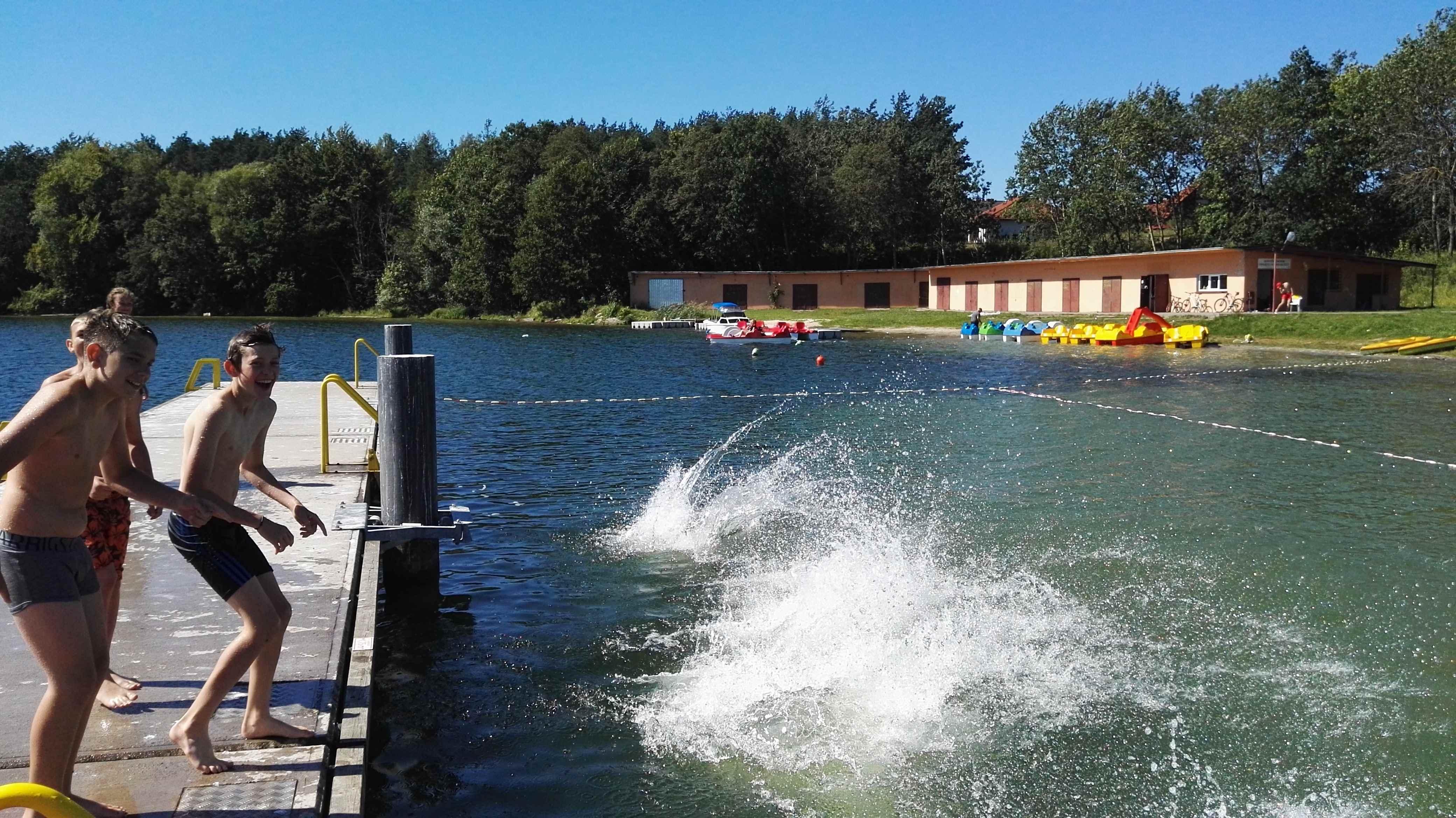 dzieci skaczą do jeziora