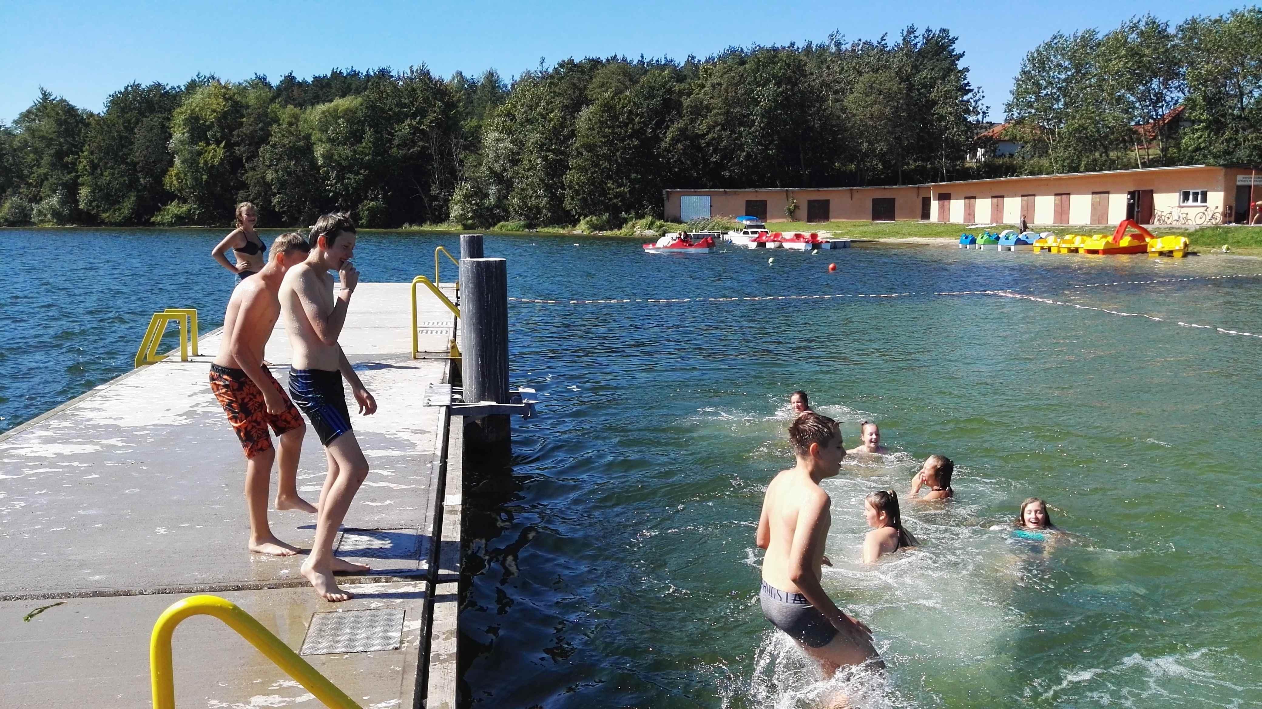 dzieci pływają w jeziorze