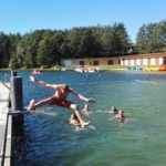 uczestnicy obozu sportowego wypoczywają nad jeziorem